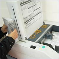印刷物チラシの折加工サービス。当社の折加工機械と作業風景画像